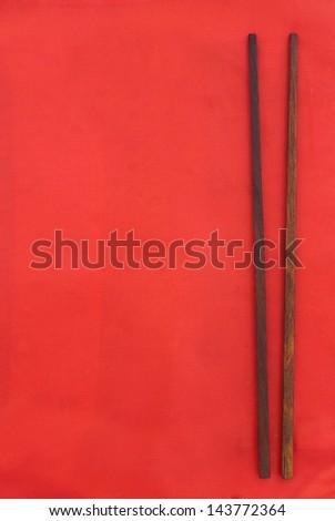 chopsticks on red background - stock photo