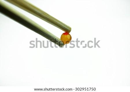Chopsticks pinch red caviar, salmon roe - stock photo
