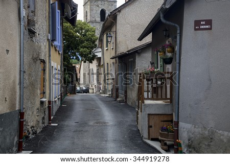 Chorges, France - June 24th, 2007: Narrow French street with two people near church, Hautes Alpes, Provence, France