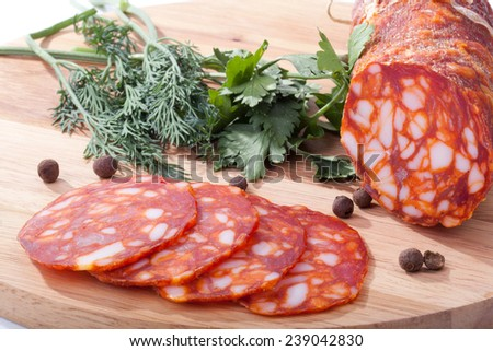 chorizo sausage with herbs and pepper on the board - stock photo