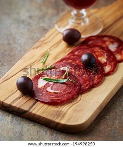 Chorizo Sausage with Olives on a Wooden Chopping Board - stock photo