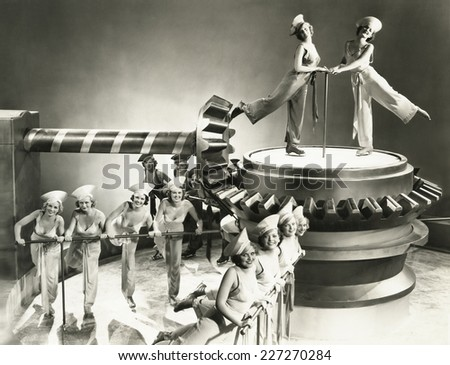 Chorus girls dancing on machine part - stock photo