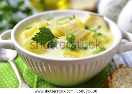 Chowder with potato,cod and green pea on rustic background. - stock photo