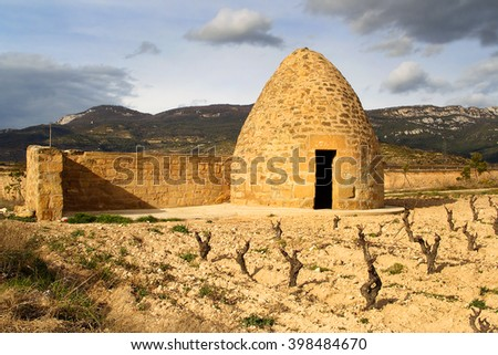 Chozo de Larrad, an old beehive-shaped shepherds hut, now surrounded by vineyards of the Ebro valley, La Rioja, Spain - stock photo