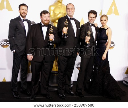 Chris Evans, Ben Wilkins, Thomas Curley, Craig Mann and Sienna Miller pose in the press room during the 87th Annual Academy Awards at Loews Hollywood Hotel on February 22, 2015 in Hollywood.