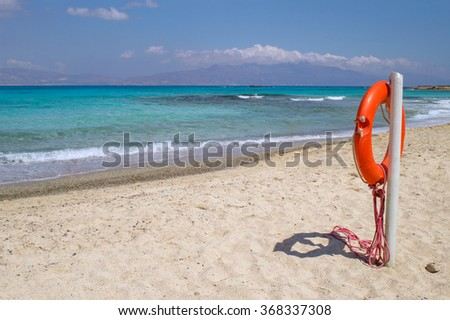 Chrisi (Chrysi) island white beach with red  life buoy in foreground, Crete, Greece. One of the most beautiful uninhabited island of Greece. - stock photo