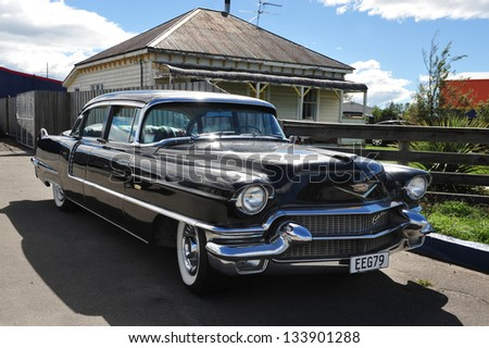 CHRISTCHURCH - MARCH 01: A classic Cadillac car parked outside an old house in Christchurch, New Zealand on March 01 2009.In NZ there are more then 13,000 vintage classic cars in immaculate condition - stock photo