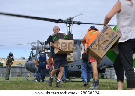 CHRISTCHURCH, NEW ZEALAND, FEBRUARY 26, 2011 - Volunteer relief workers scramble for food supplies from a RNZAF helicopter after the 6.4 earthquake in Christchurch, New Zealand, 22-2-2011 - stock photo