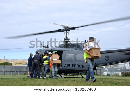 CHRISTCHURCH, NEW ZEALAND, FEBRUARY 22, 2011: Volunteer relief workers scramble for food supplies from an Air Force Iroquois helicopter after the big earthquake in Christchurch, New Zealand, 22-2-2011 - stock photo