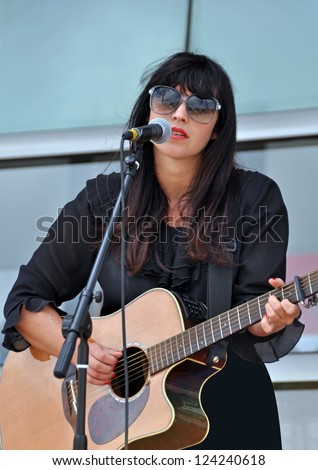CHRISTCHURCH, NEW ZEALAND - JANUARY 22, 2011: The beautiful Flip Grator singing and playing guitar at the 18th World Buskers Festival on January 22, 2011 in Christchurch. - stock photo