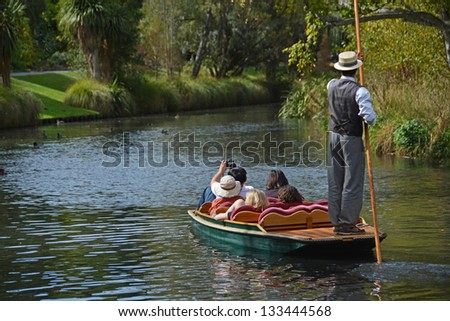 CHRISTCHURCH, NEW ZEALAND - MARCH 31, 2013: A boatman guides a group of tourists in their punt down the Avon River on Easter Sunday afternoon on March 31, 2013 in Christchurch. - stock photo