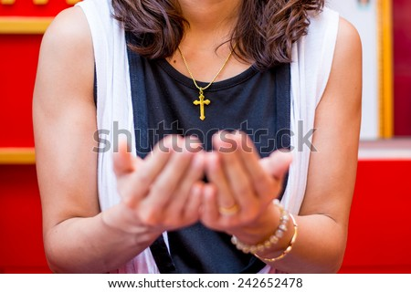 Christian believer praying to God with Cross rosary in her Neck. Focus on Cross. - stock photo