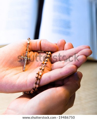 Christian believer praying to God with rosary in hand. - stock photo