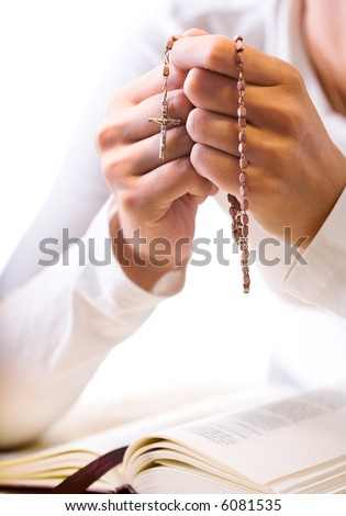 Christian believer praying to God with rosary in hand. Vertical version. - stock photo