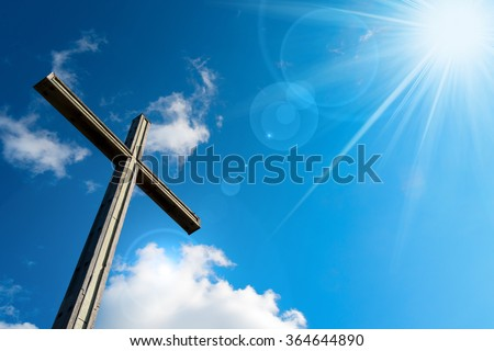 Christian Cross Against a Blue Sky / Wooden christian cross on blue sky with clouds and sun rays - stock photo
