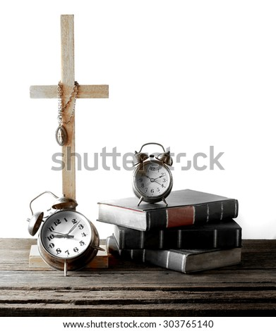 Christian cross and old three holy books stacking with big and little alarm clocks on vintage wood table over white shaded background still life concept on religious faith vintage color tone version - stock photo