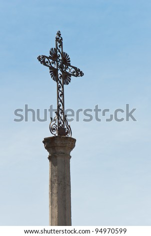 Christian cross beside a church in Venasque in France.