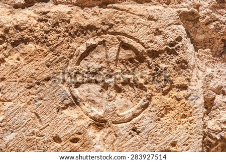 Christian cross of stone  wall of the Church of the Holy Sepulchre in the Old City of Jerusalem. - stock photo