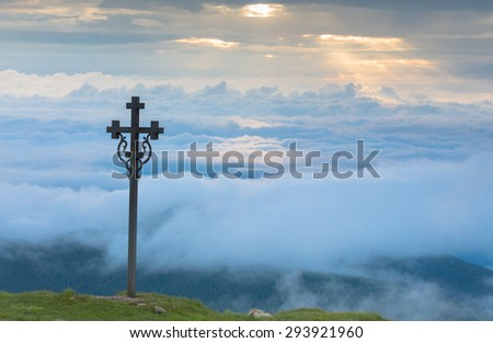 Christian cross on a background of clouds in the mountains - stock photo