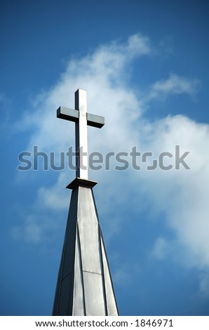Christian cross on steeple against blue sky and clouds