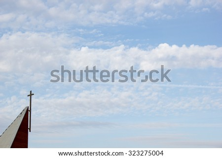 Christian cross on steeple against blue sky and clouds - stock photo