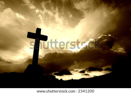 christian cross silhouette and the clouds in sepia tone
