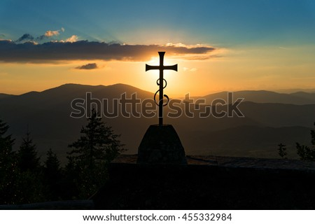 Christian cross with sunset and hills. Religious symbol against nature background