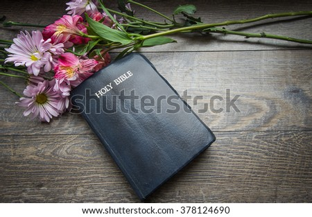 Christian Easter Holiday Background.  Bouquet of spring flowers frame a King James Bible. Shot from above on a rustic wood background. - stock photo