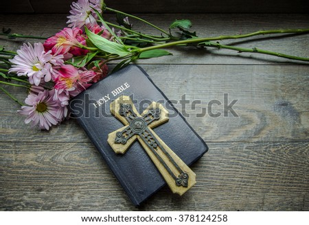 Christian Easter Holiday Background. Bouquet of spring flowers frame a King James Bible with a crucifix. - stock photo