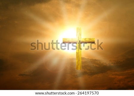 Christian gold wood cross over sunset - stock photo