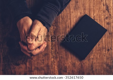 Christian man praying with hands crossed and Holy Bible by his side on wooden desk in church, top view - stock photo
