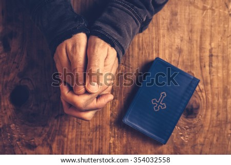 Christian man praying with hands folded and fingers crossed with Holy Bible by his side on wooden desk in church, top view - stock photo