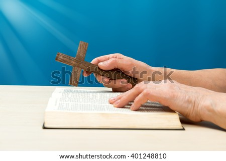Christian praying with hands folded and fingers crossed with Holy Bible by his side on wooden desk in church - stock photo
