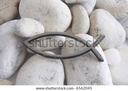 Christian religious Fish sign over white pebbles - stock photo