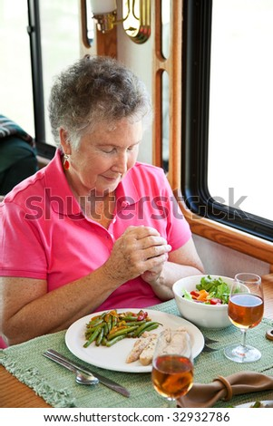 Christian senior woman saying grace over a healthy meal in her motor home. - stock photo