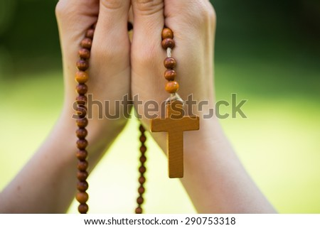 Christian woman praying with rosary in hands - stock photo