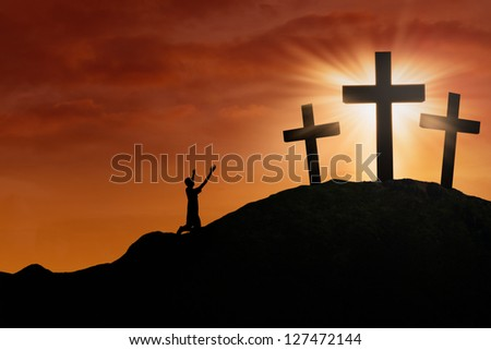 Christian worshiper is sitting on the hill beside the cross on sunset background