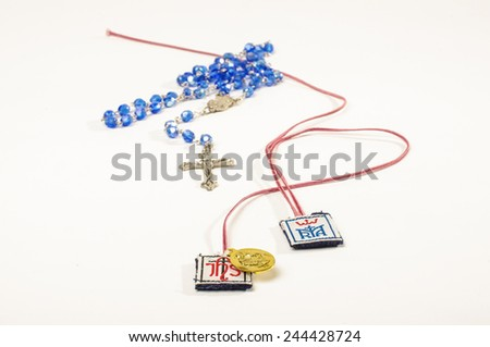 Christianity religion symbols scapulars, rosary and cross - stock photo