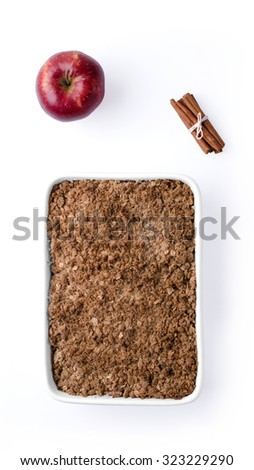 Christma still life consisting of red apple, cinammon and apple crumnle against white background. - stock photo