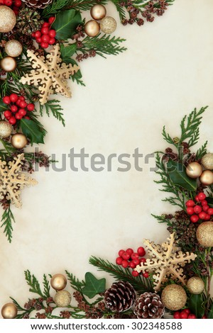 Christmas abstract background border with gold snowflake and bauble decorations, holly, fir and cedar cypress greenery over parchment paper.  - stock photo