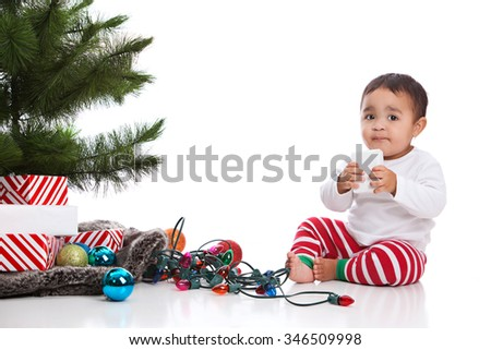 Christmas!  Adorable mixed race baby boy wearing pajamas and sitting next to the Christmas tree with presents, lights and Christmas bulbs.  Isolated on white.