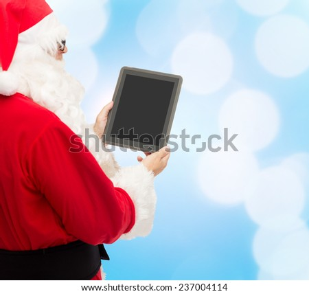 christmas, advertisement, technology, and people concept - man in costume of santa claus with tablet pc computer over blue lights background - stock photo