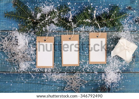 Christmas and New Year background. Christmas blank presents tags and decoration, fir branch on blue wooden background. Copy space image - stock photo