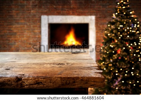Christmas and New year background with empty dark wooden deck table over christmas tree and blurred light bokeh. Empty display for product montage. Rustic vintage Xmas background.