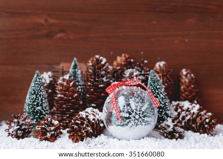 Christmas and New Year background with snow, pine cones, christmas ball with snowflake. Place for your text.