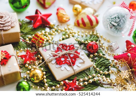 Christmas and New Year background with thuja branch, decorations and presents wrapped in craft paper with snowflakes.