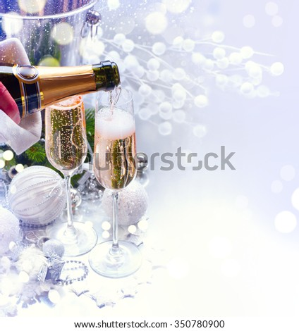 Christmas and New Year celebration with champagne. Holiday dinner table setting with Christmas decoration and sparkling wine. Champagne pouring.  - stock photo