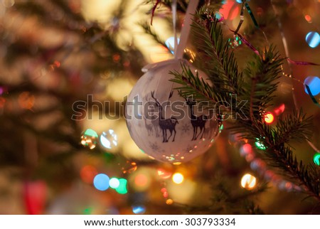 Christmas and New Year decoration. Beautiful bauble with deers hanging on the Christmas tree. Holiday glowing background. - stock photo