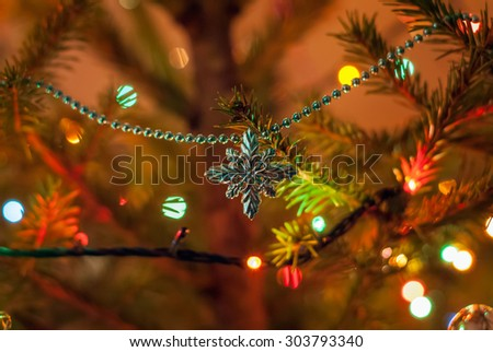 Christmas and New Year decoration. Beautiful snowflake and lanterns are hanging on the Christmas tree. Holiday glowing background. - stock photo