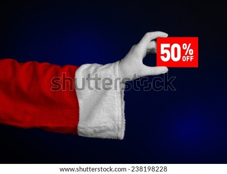 Christmas and New Year discounts topic: Hand of Santa Claus holding a red card for a 50 % discount on an isolated dark blue background - stock photo